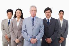 Fälliger Geschäftsmann, der zusammen mit seinem Team steht Stockfoto