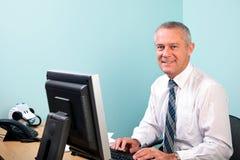 Fälliger Geschäftsmann gesessen an seinem Büroschreibtisch Stockfotografie