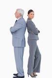 Fälliger Geschäftsmann zurück zu Rückseite mit Kollegen Lizenzfreie Stockfotografie
