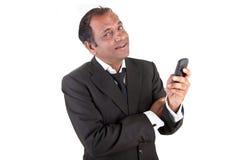 Fälliger indischer Geschäftsmann mit Handy Stockfotografie