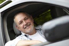Fälliger Kraftfahrer, der aus Auto-Fenster heraus schaut Stockfotos