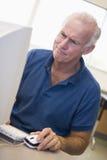 Fälliger männlicher Kursteilnehmer, der am Computerüberwachungsgerät die Stirn runzelt Lizenzfreies Stockbild