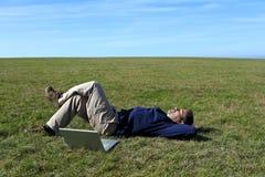 Fälliger Mann, der auf dem Gebiet nahe bei Laptop sich entspannt Stockfotografie