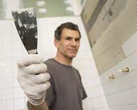 Fälliger Mann, der das Badezimmer mit Trowel mit Ziegeln deckt Stockfotos
