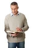 Fälliger Mann, der ein Buch liest Stockbilder