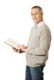 Fälliger Mann, der ein Buch liest Stockbild
