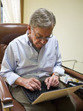 Fälliger Mann, der einen Laptop verwendet Lizenzfreies Stockbild