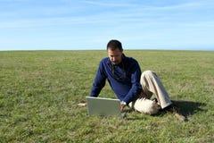 Fälliger Mann, der Laptop auf dem Gebiet verwendet Stockbilder