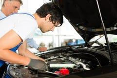 Fälliger Mann und Mechaniker, die Automotor betrachtet Stockbild