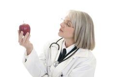 Fälliger weiblicher Doktor, der einen Apfel anhält stockfotos