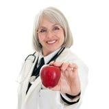 Fälliger weiblicher Doktor, der einen Apfel anhält stockbilder
