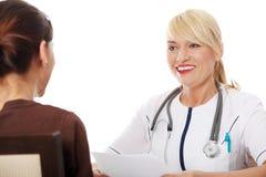 Fälliger weiblicher Doktor, der mit Patienten spricht. Lizenzfreie Stockfotografie