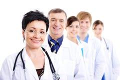 Fälliger weiblicher Doktor mit Gruppenkollegen lizenzfreies stockbild