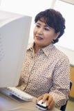 Fälliger weiblicher Kursteilnehmer, der Computerfähigkeiten erlernt Stockfoto