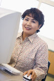 Fälliger weiblicher Kursteilnehmer, der Computerfähigkeiten erlernt Stockbild