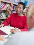Fälliger weiblicher Kursteilnehmer, der in der Bibliothek studiert lizenzfreies stockfoto