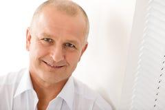 Fälliges Geschäftsmannlächeln, das Nahaufnahmeportrait aufwirft Stockfoto