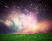 Fält av gräs under dröm- galaxhimmel, utrymme, glödande stjärnor Arkivbilder