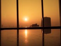 Fält av röda vallmo Konturer av det glass fönstret med orange soluppgångbakgrund Sikt från hög kontorsbyggnad Royaltyfri Fotografi