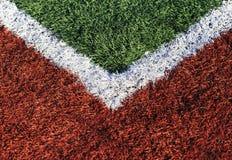 Fält för fält för fotboll grön och röd fotboll, i solig dag Fotografering för Bildbyråer