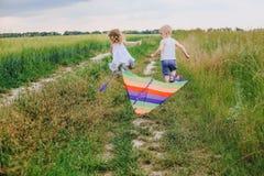 Fält för gräs för flicka för flygdrakepojke litet royaltyfria foton