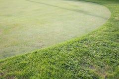 Fält för grönt gräs av golfbanan Arkivfoto