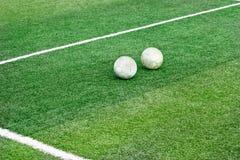Fält för grönt gräs med den vita fläcklinjen och gammal fotboll för fotboll två Fotografering för Bildbyråer