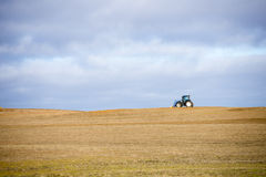 Fält för skörd för traktorsned boll öppet i lantligt lantgårdområde Arkivbilder