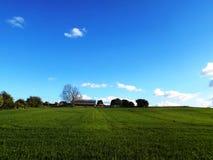 Fält med den avlägsna lantgården på Crookham, norr Northumberland, England royaltyfri bild