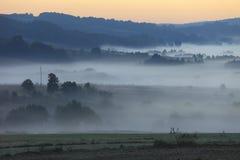 Fält och ängar under otta fördunklar - den Podkarpacie regionen, det Lesser Poland landskapet, Polen Royaltyfri Foto