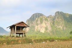 Fält och berg och stuga Arkivbild