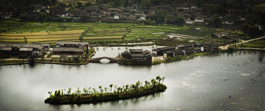 Fält och kinesisk by vid floden Arkivfoto