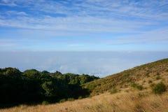 Fält på berglandskap, mist och blå himmel Royaltyfria Bilder