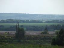 Fältet korsas av järnvägen Arkivbild