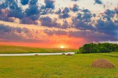 Fältlandskap med floden och hö royaltyfri foto