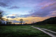 Fältväg för två spår till soluppgång Fotografering för Bildbyråer