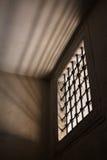 Fängelsecell med ljust skina till och med ett gallerförsett fönster arkivfoton