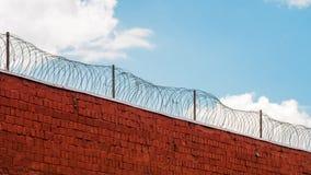 Fängelsevägg med taggtråd och moln på bakgrunden arkivbild