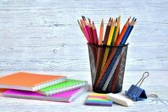 Färben Sie Auflagen und farbige Bleistifte in einem Behälter, in einem Radiergummi und in einem Papier Stockfotos