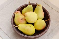Färben Sie Birnen in der alten hölzernen Schüssel gelb Stockfoto