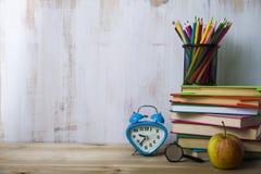Färben Sie Bleistifte auf einem Stapel von Büchern auf einem hellen Holztisch Stockbild