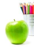 Färben Sie Bleistifte in den Blechdose- oder Bleistifthaltern und im grünen Apfel, BAC Stockbild