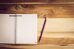 Färben Sie Bleistifte in den Schalen und im Notizbuch, die auf einen Schreibtisch gesetzt werden Lizenzfreies Stockbild