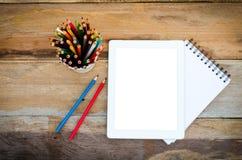 Färben Sie Bleistifte in den Schalen und im Notizbuch, die auf einen Schreibtisch gesetzt werden Lizenzfreie Stockfotos