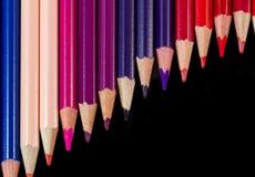 Färben Sie Bleistifte in der diagonalen Bildung lokalisiert auf schwarzem warmem palet stockbild