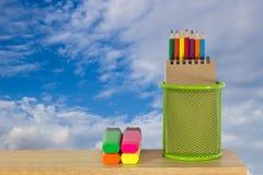 Färben Sie Bleistifte in einem grünen Halterkorb mit Markierungsstiften Lizenzfreies Stockfoto