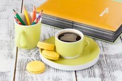 Färben Sie Bleistifte in einer grünen Schale mit grünlichem Becher Kaffee Stockbild