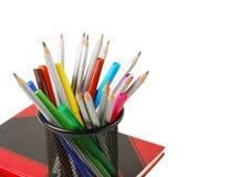 Färben Sie Bleistifte, Filzstifte, Bürsten und Stifte über dem Notizbuch, das auf Weiß mit Raum für Text lokalisiert wird Stockfotos