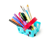 Färben Sie Bleistifte, Filzstifte, brushesin, das ein blauer Spielzeugkorb auf weißem Hintergrund lokalisierte Schuleinkaufsthema Lizenzfreies Stockfoto