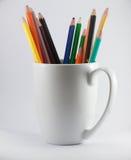 färben Sie Bleistifte gebrochen auf weißem Becher und auf weißem Hintergrund Lizenzfreies Stockfoto